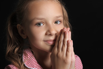 Praying little girl on dark background