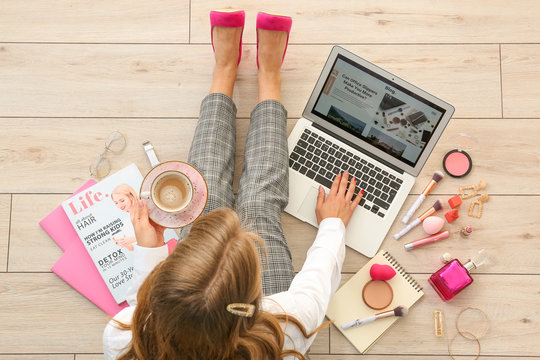 Female beauty blogger with laptop and cup of coffee sitting on wooden floor, top view