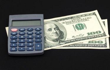 Two hundred dollar bills and calculator isolated on black background