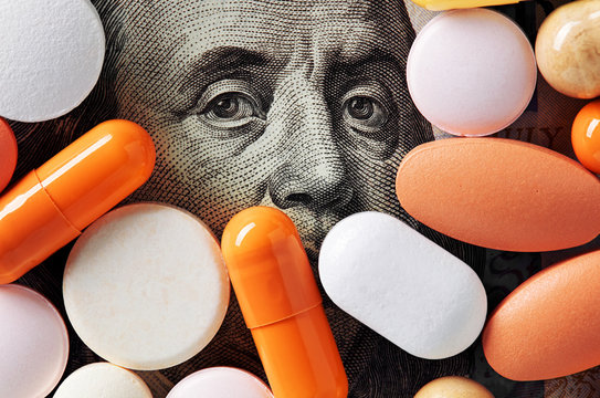 Capitalism and healthcare policy concept. Colorful medical pills cover Benjamin Franklin's face on one hundred american dollar bill. Macro top down view.