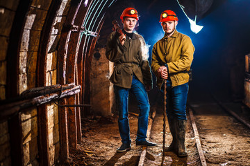 Two miners in the mine. Hard work in a coal mine. Copy space. Tired workers in a coal mine.