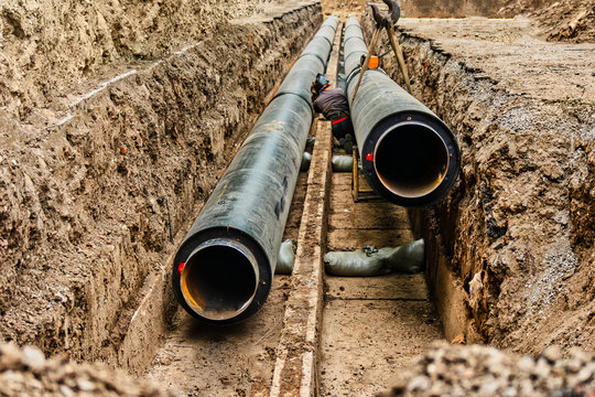 Water pipes in ground pit trench ditch during plumbing under construction repairing. Underground pipe being fixed in trench