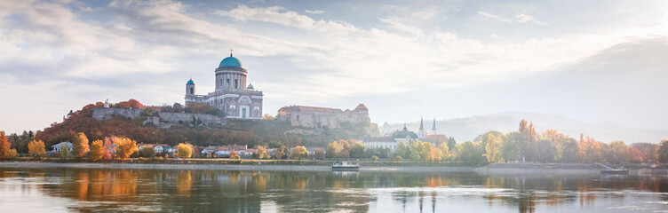 Esztergom, Hungary, view on Basilica. Beautiful light Morning misty panorama over Danube river on border of Hungary and Slovakia. Banner for web-design format photo. Autumn season, yellow trees.