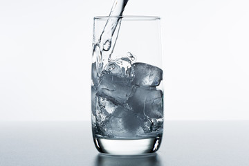 Beautiful splash of water in a glass with ice