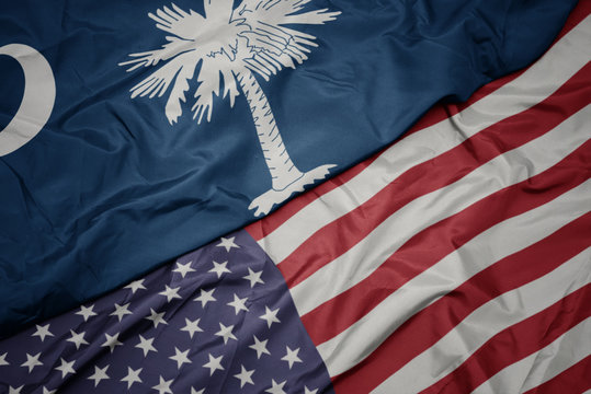 waving colorful flag of united states of america and flag of south carolina state.