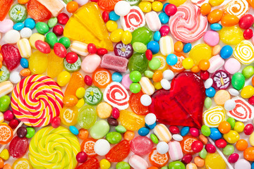 Fototapete - Colorful lollipops and different colored round candy. Top view.