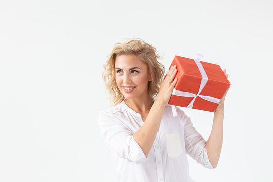 Holidays concept - Portrait of a smiling cute woman opening gift box isolated on a white background with copyspace
