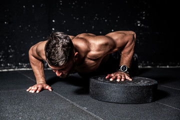 Young strong sweaty focused fit muscular man with big muscles performing push ups with one hand on...