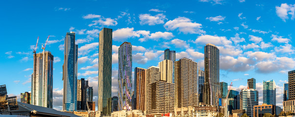 Melbourne, Australia, city skyline glowing in the late afternoon sun against a blue sky with light clouds.