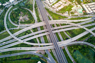 Fotobehang - Aerial view of road interchange or highway intersection with busy urban traffic speeding on the road. Junction network of transportation taken by drone.
