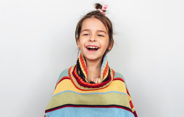 Portrait of a happy little girl smiling and laughing, playing with big colorful sweater in a holiday time, posing on gray studio background. Adorable child peeks out of a sweater has positive emotion. Wall mural