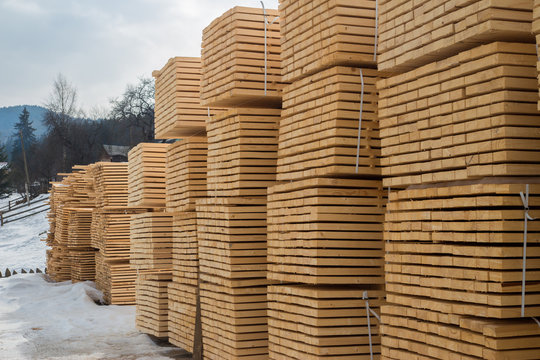 Lumber warehouse in the open air. Wooden beam, planks of wood, stacked in stacks. Construction material
