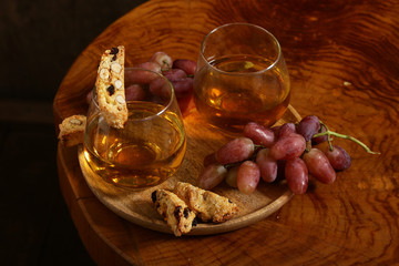 dessert white wine and biscotti on a wooden table