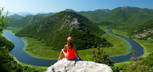 touristic woman on the rock at the top of panoramic of lake skadar in Montenegro