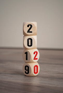 Tower made of cubes and dice with 2019 and 2020 on wooden background