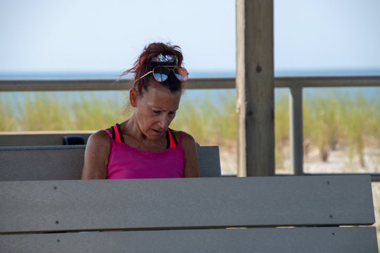Baby Boomer mature Caucasian woman Sitting on a gray bench looking down with a worried look on her face. There is a beach sand dune and the ocean behind her