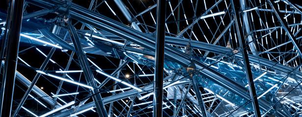 Luminous metal construction of randomly intersecting lines.