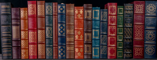 A stack of beautiful leather bound books with golden decoration against a black background.