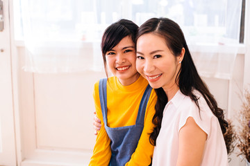 Asian middle-aged mother and teenage daughter smiling happily and looking at camera in indoors living room environment - with copy space