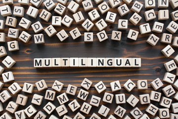 multilingual - word from wooden blocks with letters, use many  different languages multilingual concept, random letters around, white  background