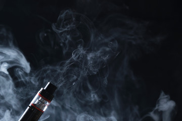 Electronic cogarette vape on a dark background with steam