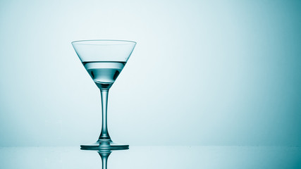Martini glass on color background