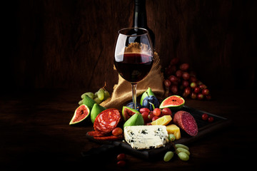 Red wine glass and appetizers, cheese, salami, figs, grapes, vintage wooden table background, selective focus, copy space
