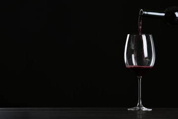 In de dag Alcohol Pouring wine from bottle into glass on table against black background, space for text