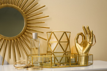 Composition with golden accessories and jewelry on dressing table near color wall