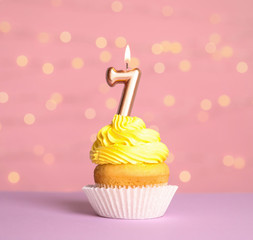 Birthday cupcake with number seven candle on table against festive lights