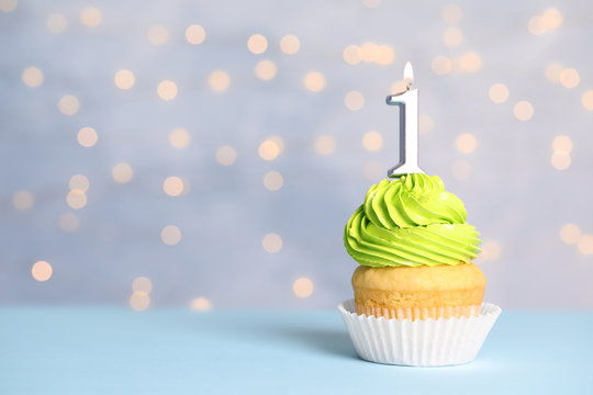 Birthday cupcake with number one candle on table against festive lights, space for text