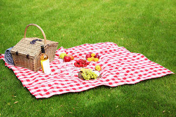 Fotobehang Picnic basket with products and bottle of wine on checkered blanket in garden