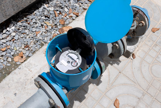 Water meter and metal pipes blue color for measurement of water flow. Water environmental conservation and water resource management concept.
