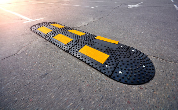 Speed bump on asphalt road. Speed Limit Tool in a city.