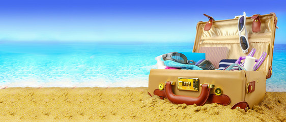 Full open suitcase on tropical beach background, banner
