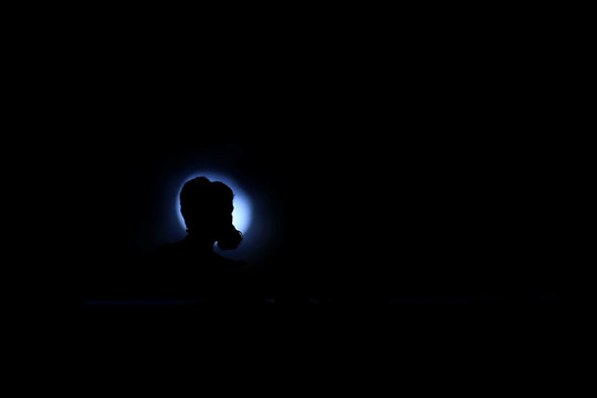 An anti-extradition bill protester is silhouetted in front of the moon, during the march to demand democracy and political reforms, in Hong Kong