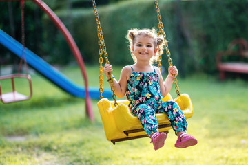 Happy little girl on a swing in the park