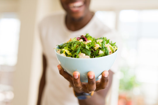 African young man holding a bowl of healthy salad smiling cheerful