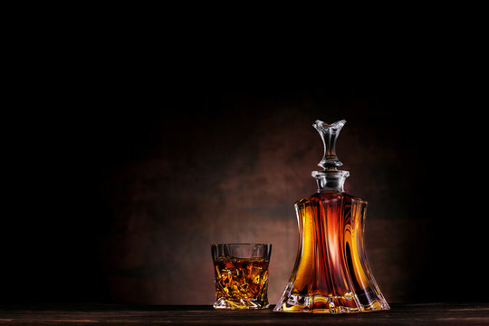 Glass of whiskey with ice and decanter on dark wood background