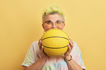 happy excited glamour cool senior holding basketball - isolated on yellow background. lifestyle,...