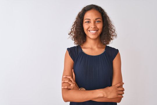 Young brazilian woman wearing blue dress standing over isolated white background happy face smiling with crossed arms looking at the camera. Positive person.