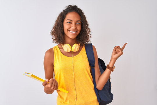 Brazilian student woman wearing backpack holding notebook over isolated white background very happy pointing with hand and finger to the side