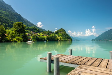 Zelfklevend Fotobehang Olijf View of Brienz lake with clear turquoise water. Wooden pier. Traditional wooden houses on the shore of Brienz lake in the village of Iseltwald, Switzerland
