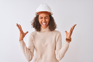 Young brazilian architect woman wearing security helmet over isolated white background celebrating mad and crazy for success with arms raised and closed eyes screaming excited. Winner concept