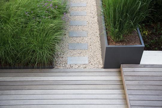 Moderne Garten- und Terrassengestaltung im Materialmix: Terrassen aus Holz und Gehweg aus Steinplatten umgeben von Schotter und Metall Pflanzgefäßen mit Grünpflanzen
