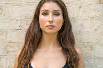 Closeup portrait of an attractive young brunette in a tank top shirt