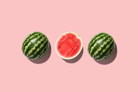 Three halves of watermelon in a row isolated on pink background.