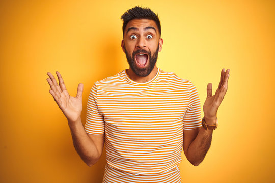 Young indian man wearing t-shirt standing over isolated yellow background celebrating crazy and amazed for success with arms raised and open eyes screaming excited. Winner concept
