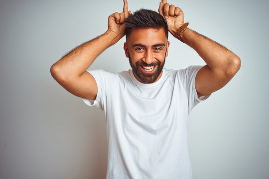 Young indian man wearing t-shirt standing over isolated white background doing funny gesture with finger over head as bull horns
