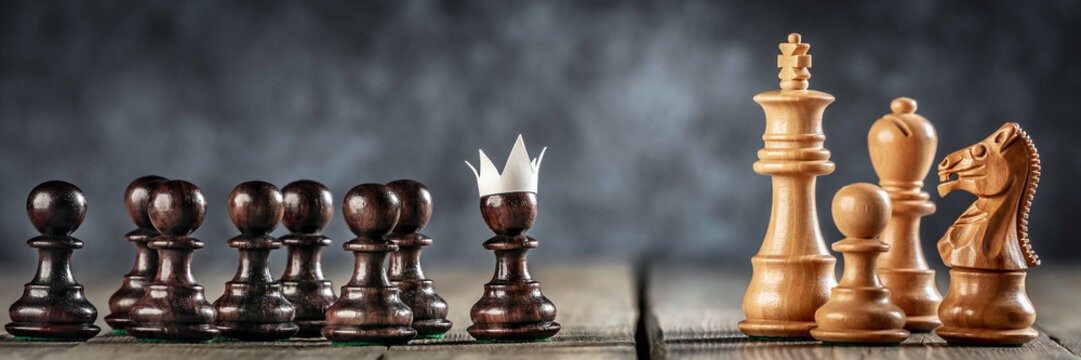Small Courageous Pawn With Fake Paper Crown Costume Leading Others Into Battle Against The Enemy - Business Entrepreneur / Leadership Concept